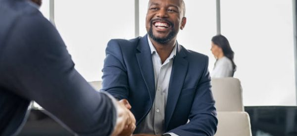 Two happy mature business men shaking hands in modern office. Successful african american businessman in formal clothing closing deal with handshake. Multiethnic businessmen shaking hands during a meeting.